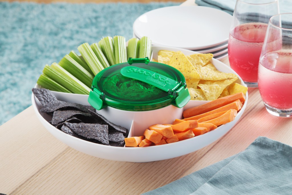 Chips and veggies sit in a serving tray with Guac-Lock's guacamole preservation container