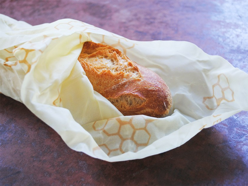 A baguette is wrapped in yellow beeswax bread wraps from Bee's Wrap