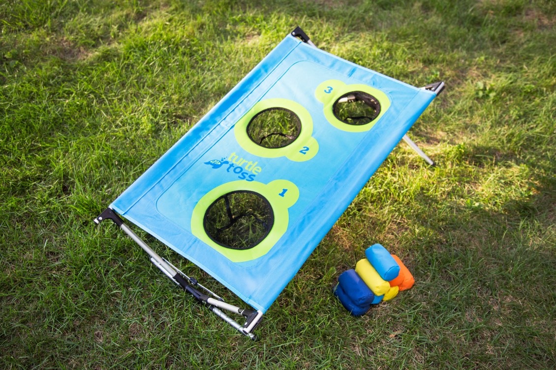 Turtletoss portable cornhole set sits on a lawn