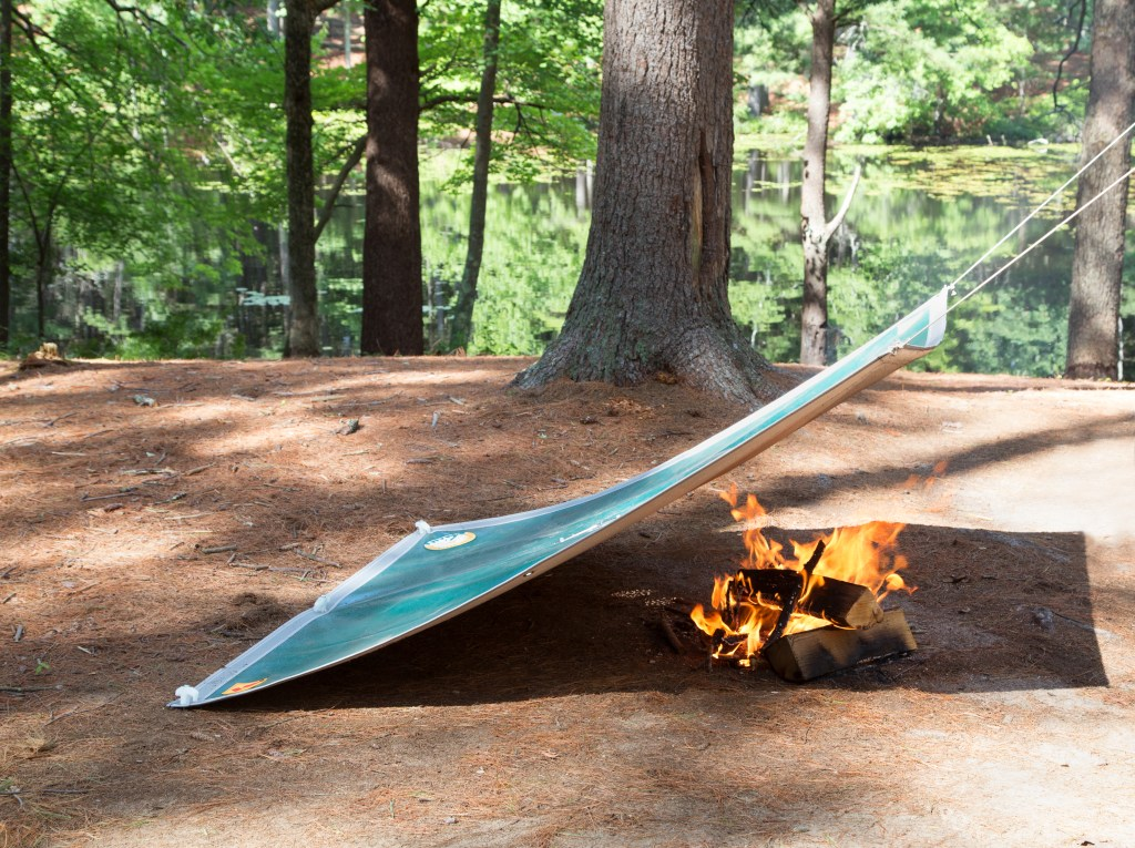 Woodland campers shield their fire from wind thanks to Campfire Defender's safety cover