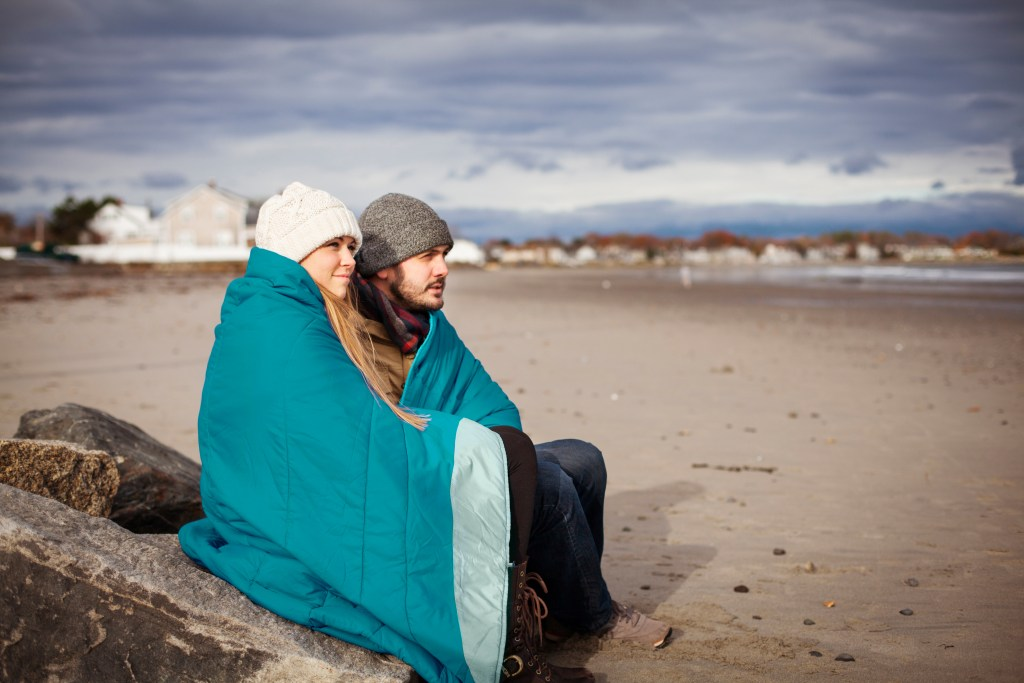 A couple sits perched on a rock at the beach in winter wrapped in a teal puffin blanket from NEMO