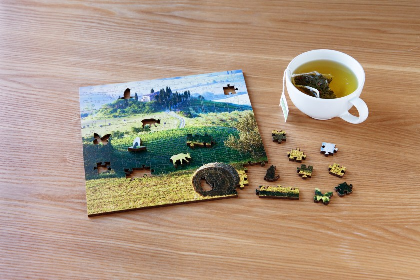 A mostly finished wooden jigsaw puzzle depicting a field scene from Zen Art & Design sits on a coffee table next to a cup of tea