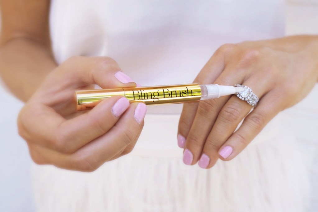 A woman uses Baublerella's Bling Brush to polish her diamond ring