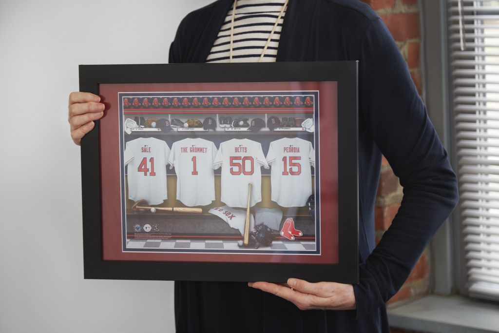A woman holds a framed personalized locker room print of the Red Sox