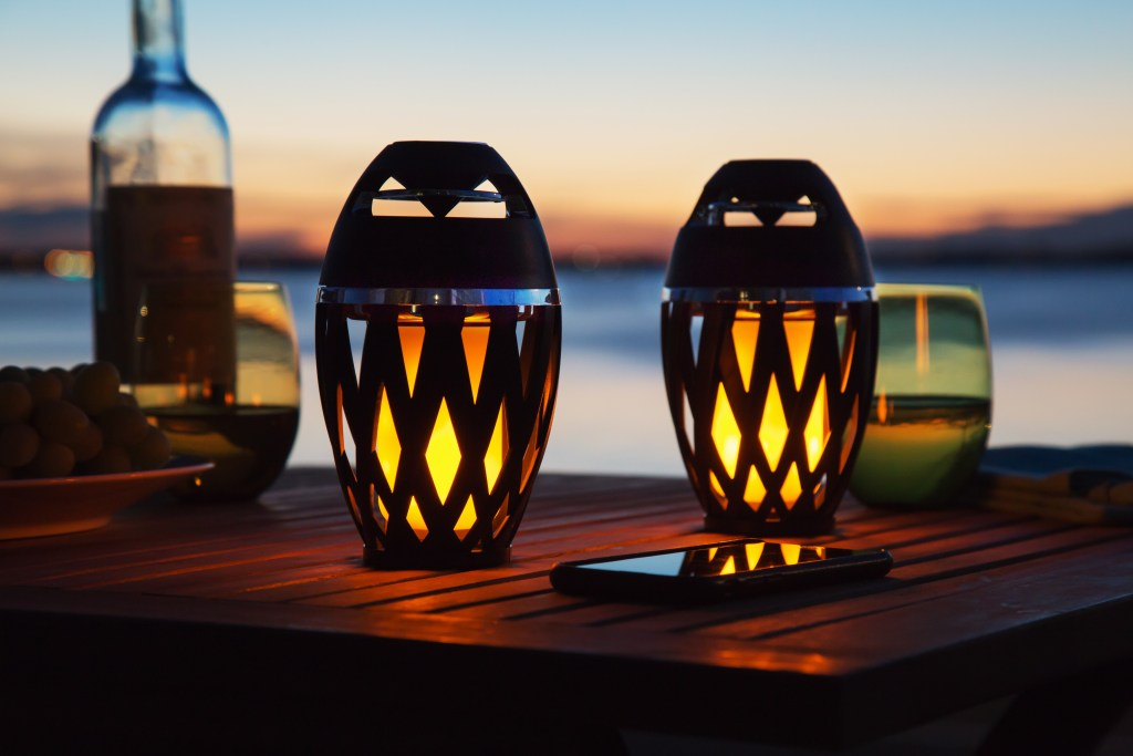 Two Tiki Tunes LED Speakers sit on a table at sunset