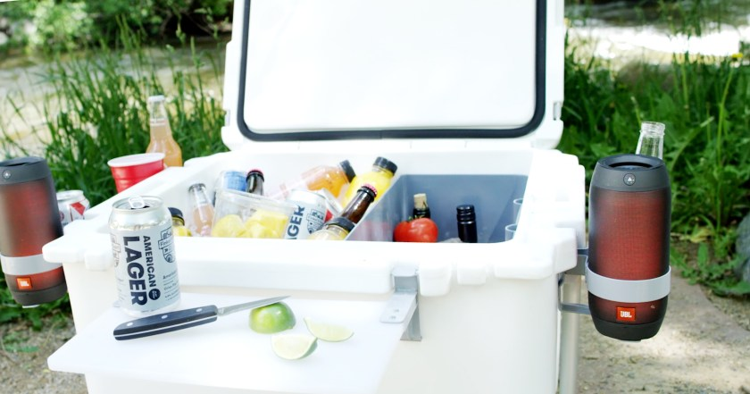 A RovR high performance cooler sits stocked with refreshments in the sand