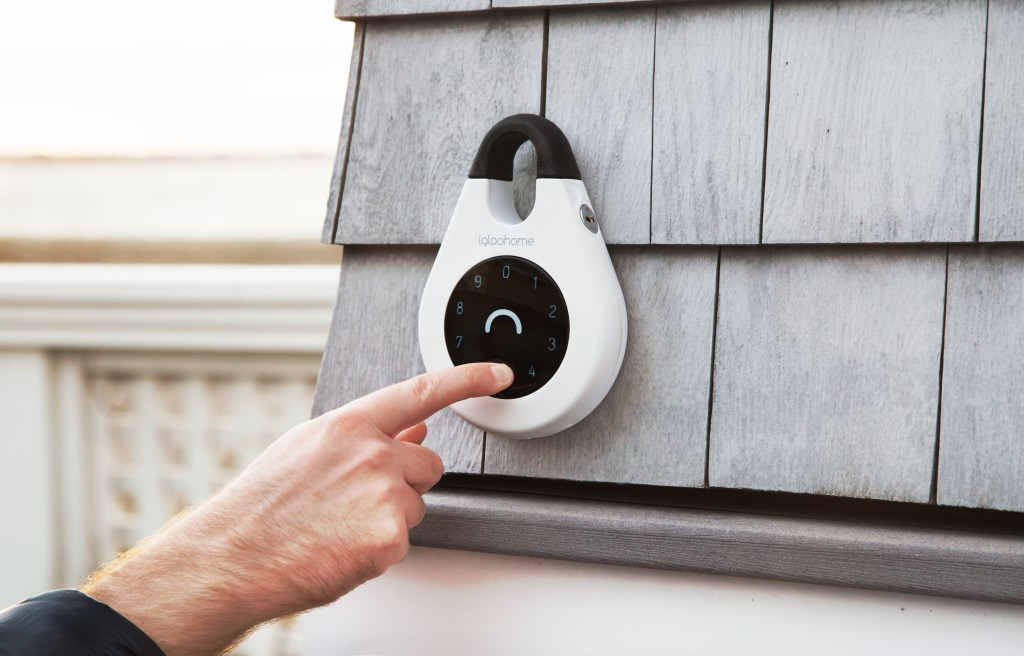 A man locks his house with an IglooHome smart key lock box