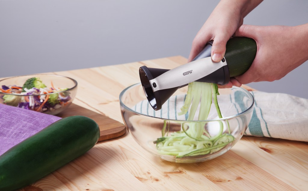 A person uses Spirelli's spiral slicer  to spiralize fresh zucchini