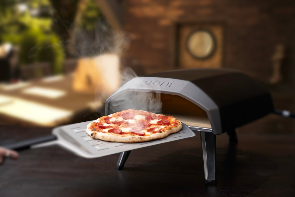 A piping hot pepperoni pizza can be seen being removed from Ooni's Koda outdoor gas pizza oven