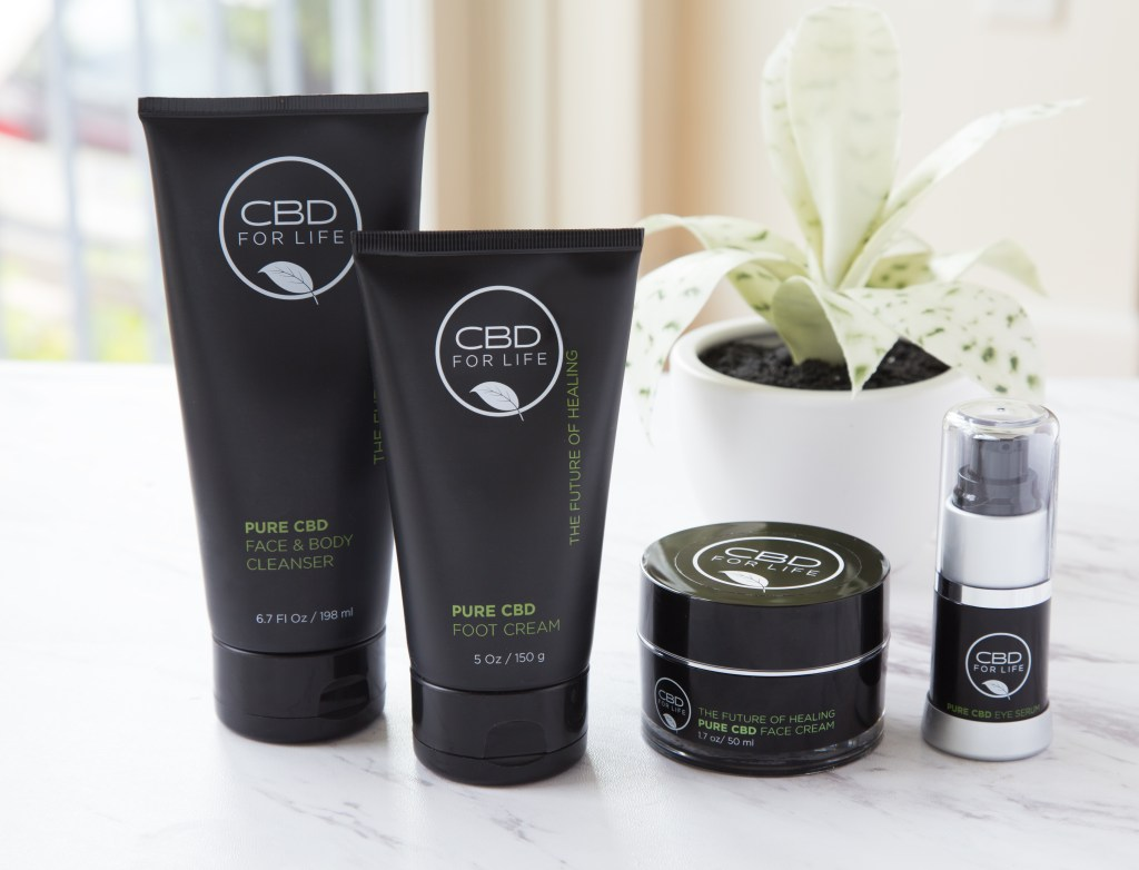4 CBD For Life skincare products sit on a marble counter next to a potted plant