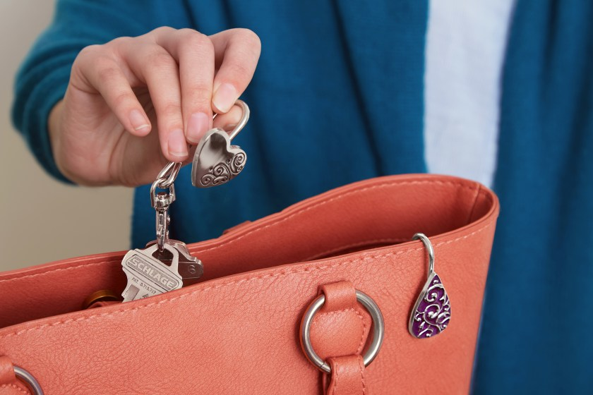 A woman is seen easily pulling her keys out of her purse with a Finder's Key Purse key hook
