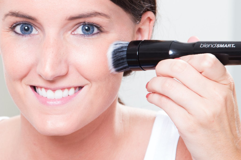 A woman is seen applying her foundation with BlendSmart's rotating makeup brush