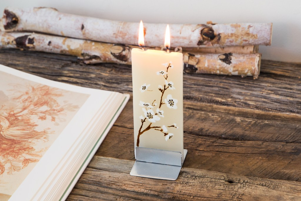 A hand-painted flat candle from Flatyz with white orchid design sits lit on a wooden table