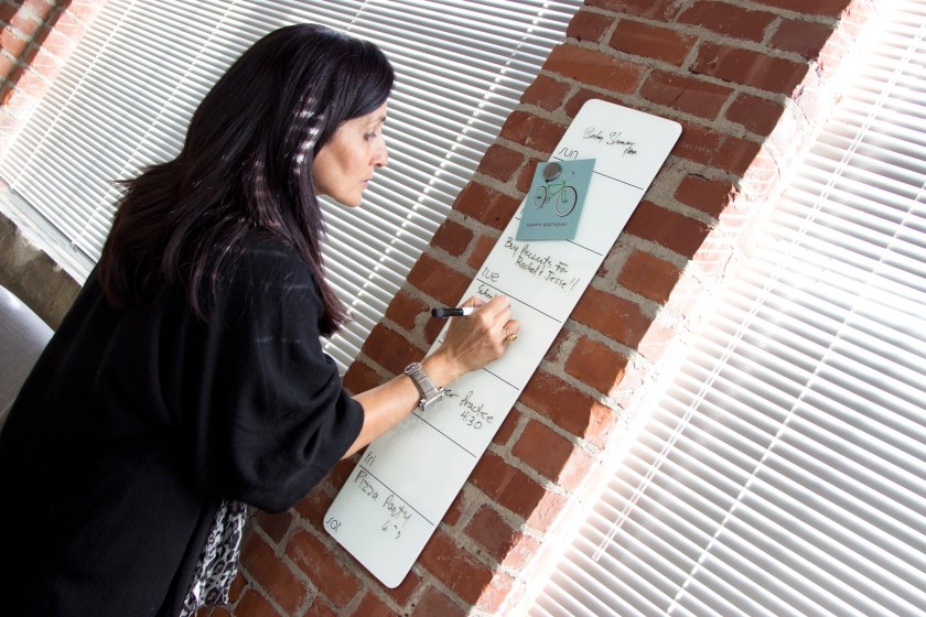 A woman is seen writing on a dry erase planner by Three By Three