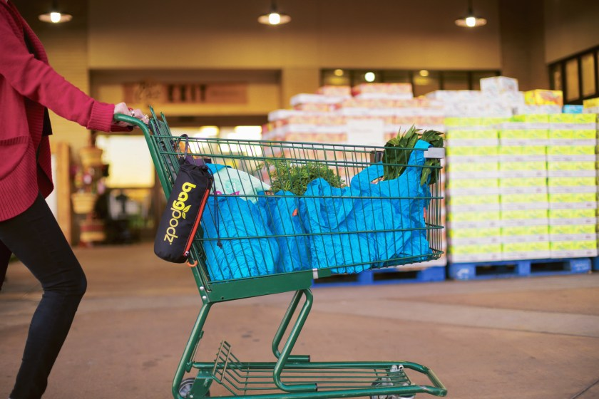 A woman pushes a shopping cart with blue reusable BagPods holding her groceries
