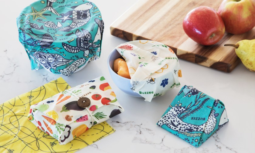 A variety of fresh foods sit on a counter wrapped in colorful beeswax food wrap from Buzzee Wraps