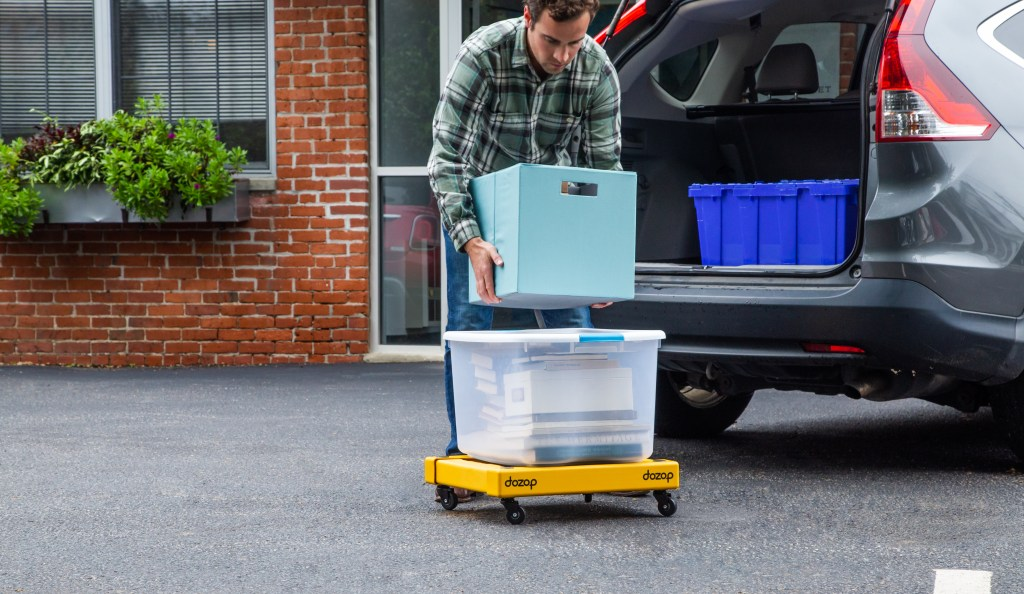 A man unloads boxes from his car using Dozop's collapsible dolly