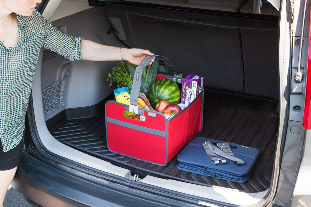 A woman uses meori's red reusable storage boxes to load groceries into her car