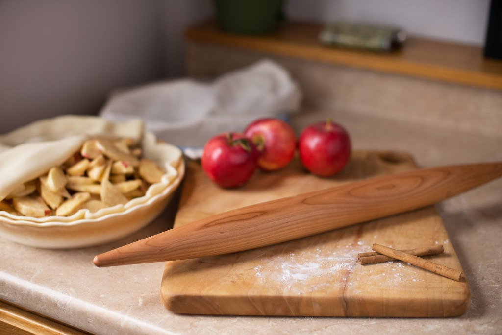 An unbaked pie sits on a counter next to ingredients & a Vermont Rolling Pins French rolling pin