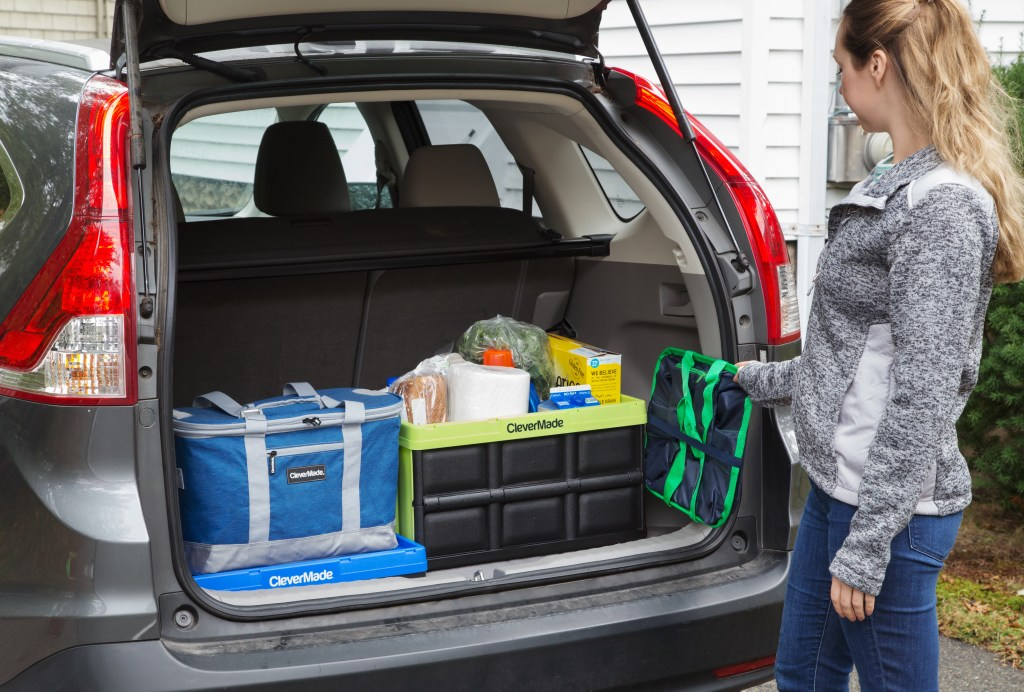A woman is seen organizing groceries in her trunk with CleverMade's collapsible crates