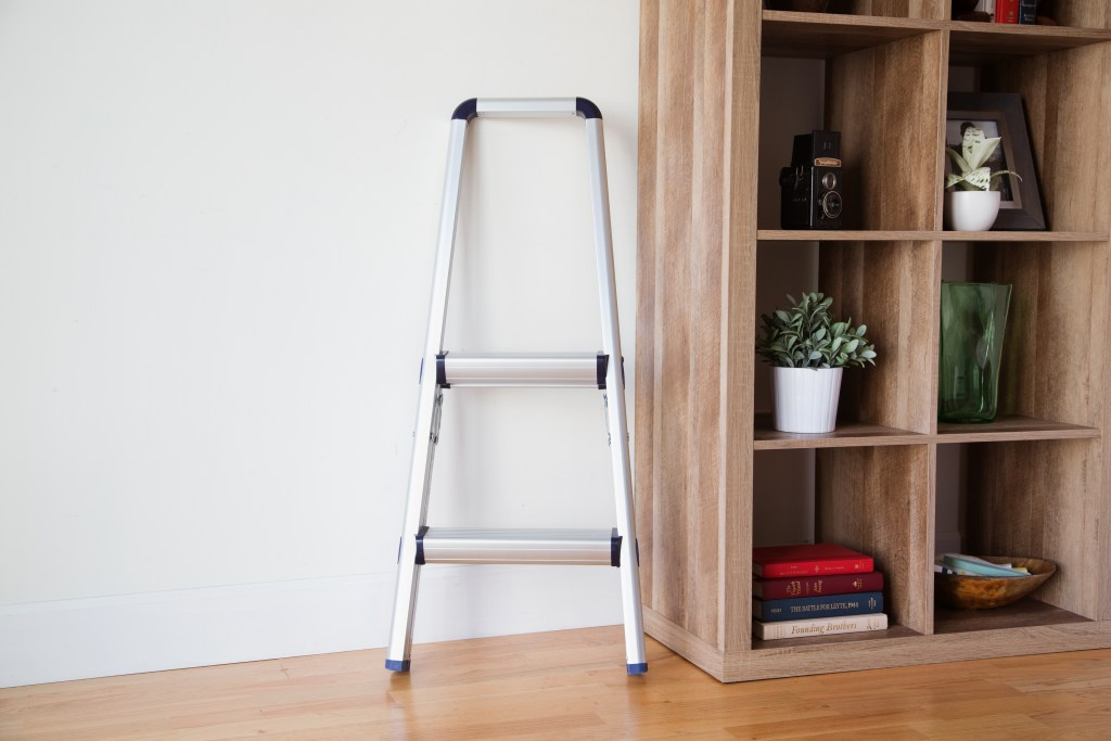 A telescoping stepstool from Xtend + Climb is seen perched against a wall