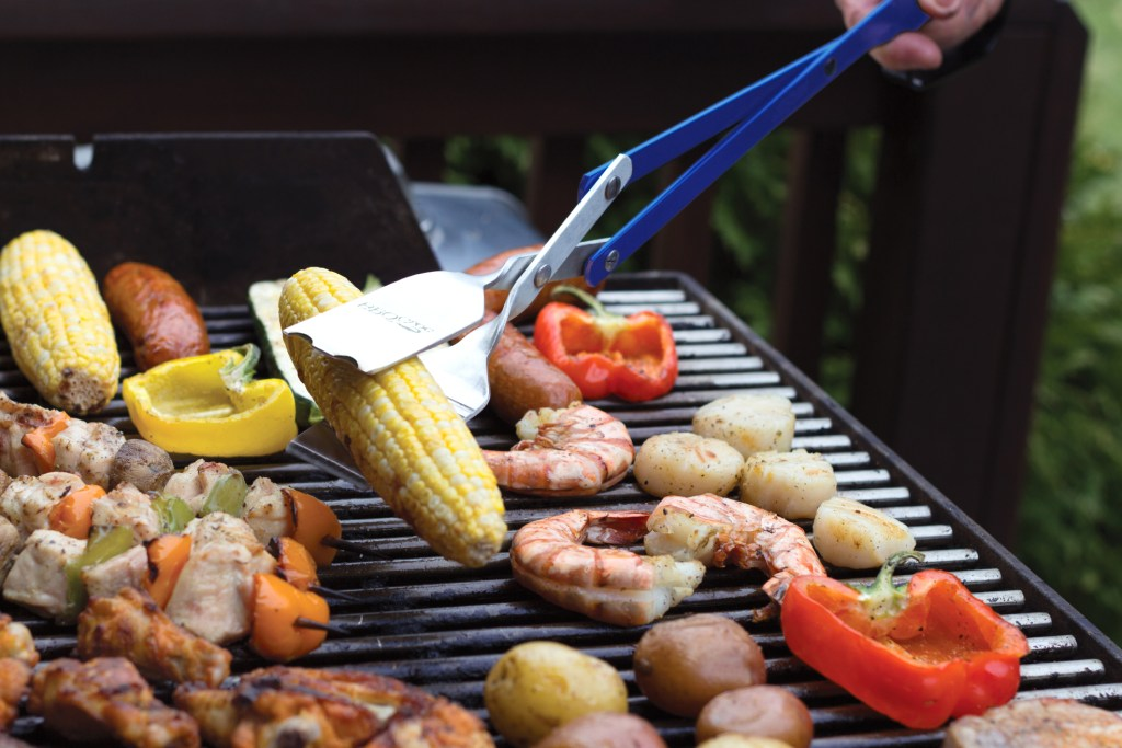 A person uses the 3-in-1 BBQ tool from BBQ Croc to pick up a corn cobb from a grill filled with other meats and veggies