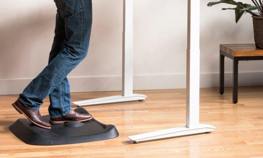 A man is seen standing on an ErgoDriven anti-fatigue standing desk mat while working