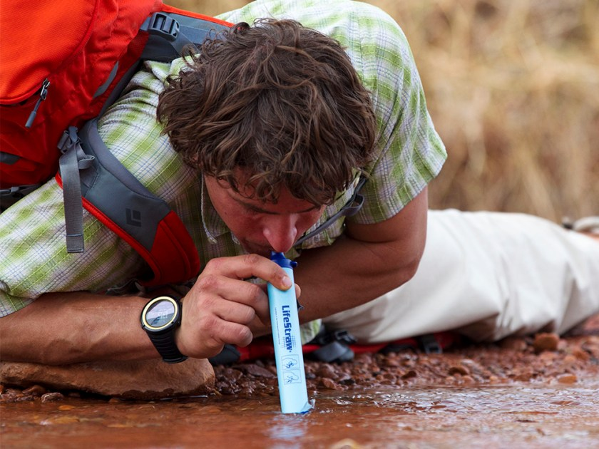 A man is seen drinking out of a puddle using LifeStraw's personal filtration straw