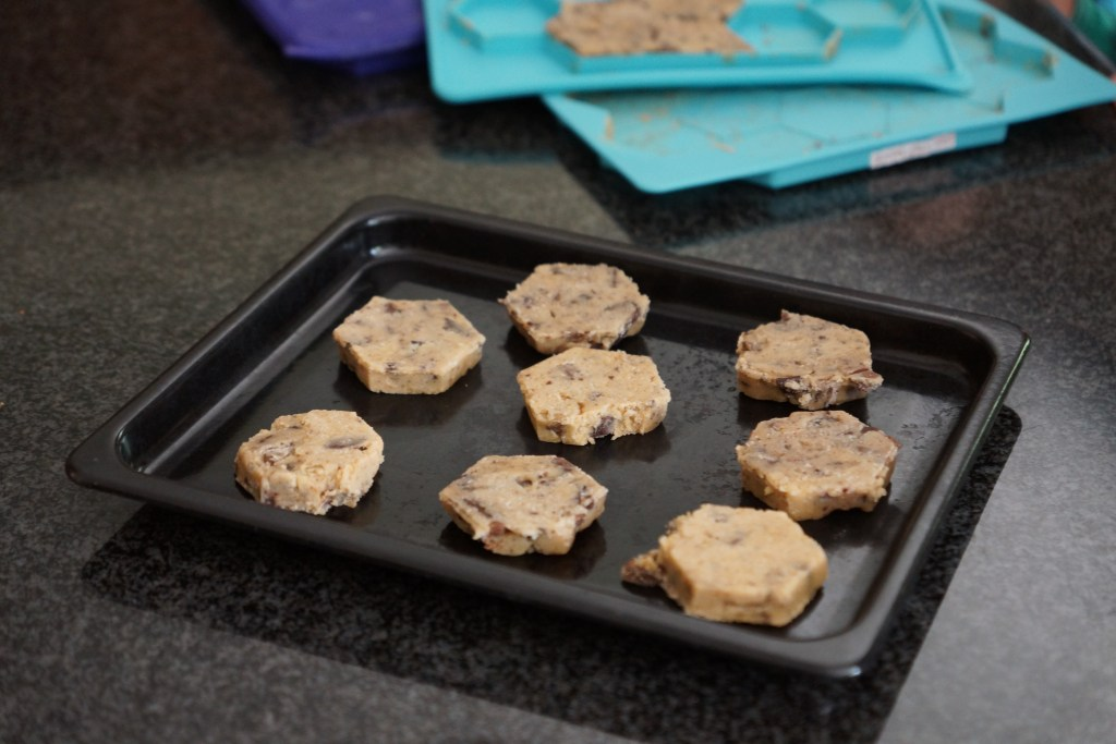 Unbaked cookies are seen on a baking sheet, having been formed in a Shape + Store cookie shaping tray