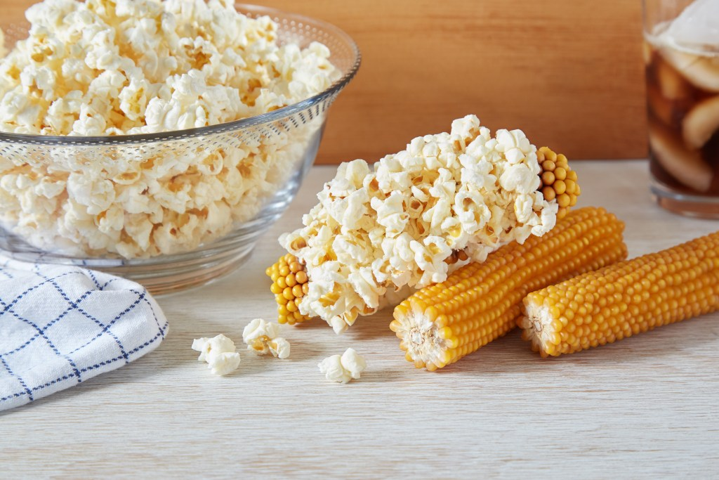 Freshly popped popcorn sits in a bowl next to unpopped Farmer's popcorn cobs from Sunflower Food Co