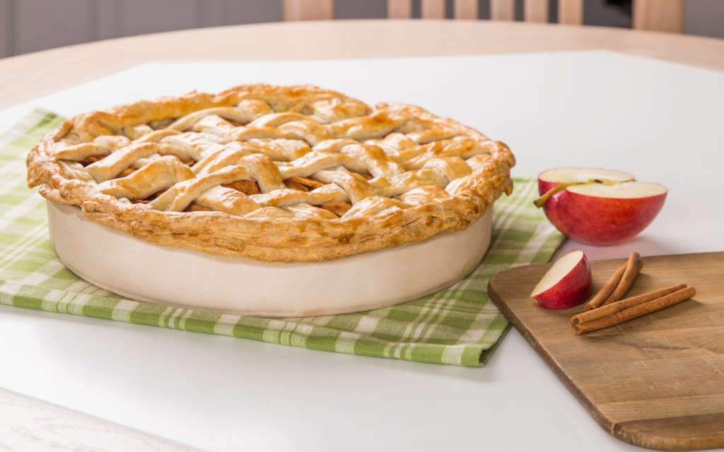 A perfectly baked apple pie sits in a superstone pie baking dish from Sassafras