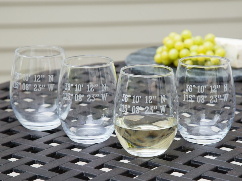 Four custom latitude & longitude stemless wine glasses from Susquehanna Glass Company sit on a patio table