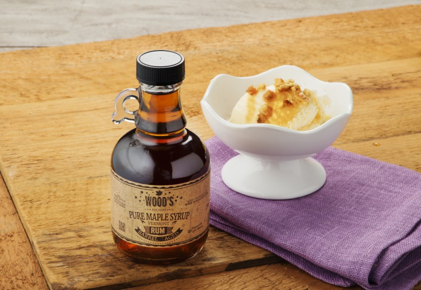 A bottle of Rum-infused Wood's maple syrup sits next to a bowl of ice cream