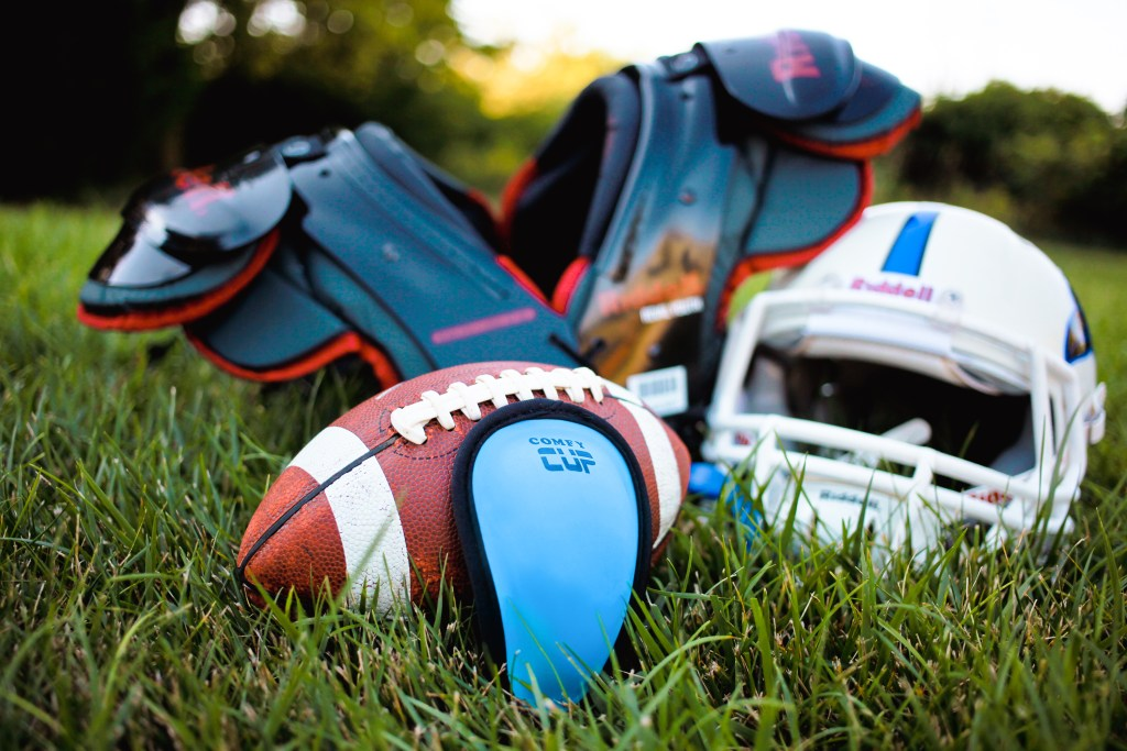 A blue youth athletic cup from Comfy Cup lays in the grass next to football gear