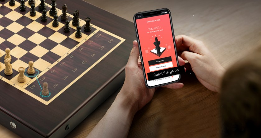 A person is seen using their smart phone to play a game of chess with  Square Off's automated smart chess board