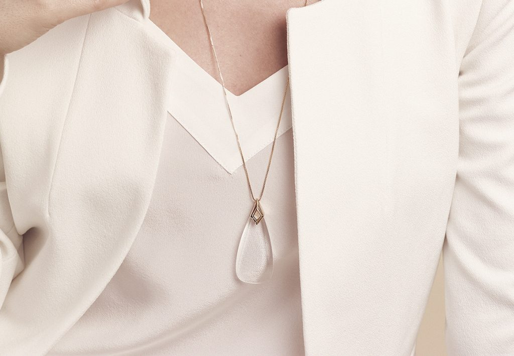 A woman wearing a white blouse & blazer is seen wearing an Amelia monocle necklace from Moderne Monocle