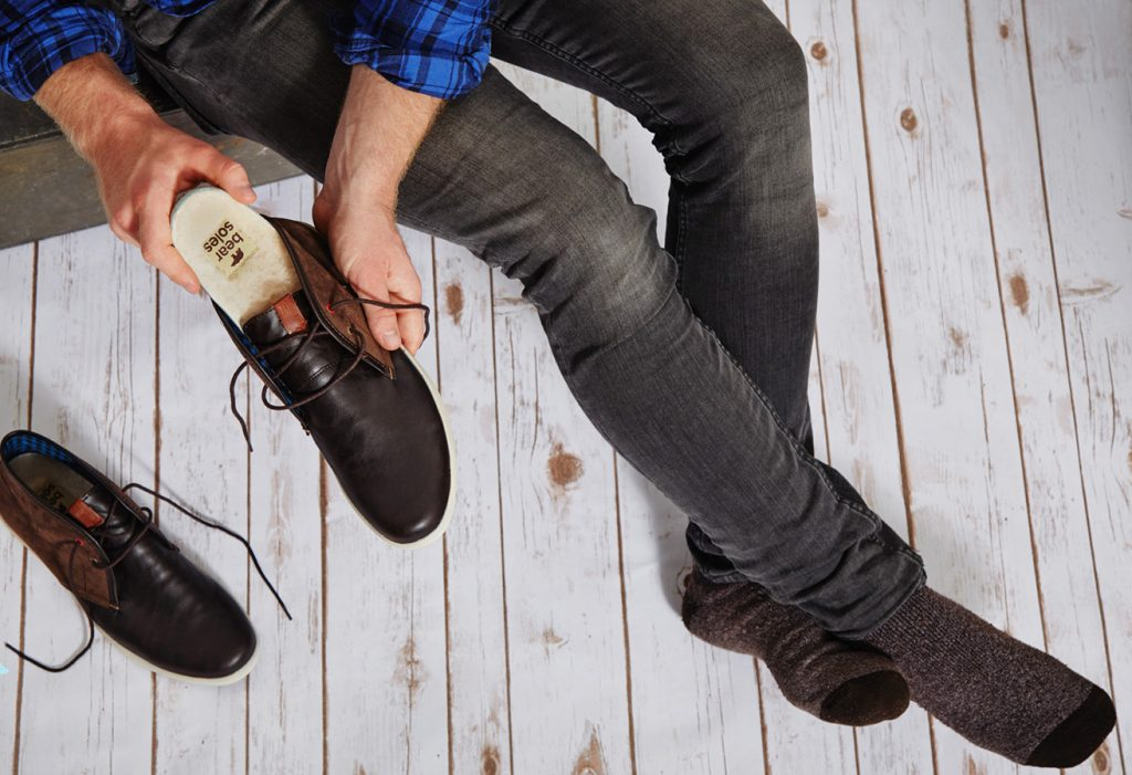 A man is seen slipping a sheepskin insulated cork insole from Honeysoles into his shoes before putting them on