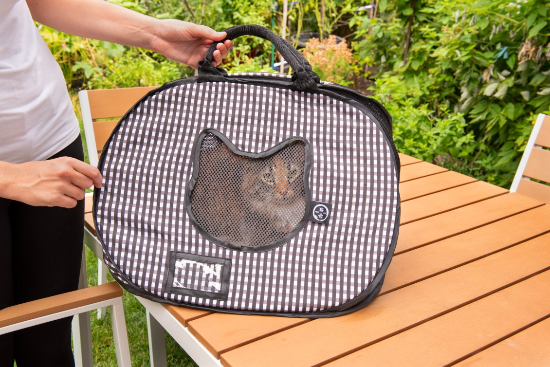 A Calico cat is seen sitting in a black & white checkered ultra-light collapsible cat carrier from Necoichi