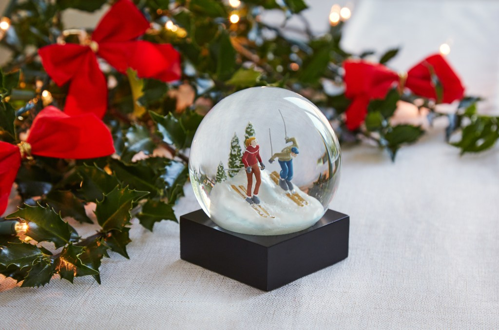 Skiers are seen skiing down a snowy mountain in a CoolSnowGlobes idyllic scene