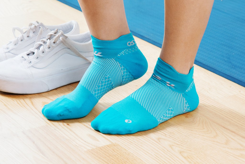 A woman is seen wearing teal plantar fasciitis compression socks from OS1st
