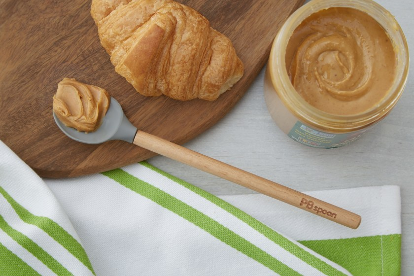 A scoop of peanut butter sits on a PBSpoon next to a croissant