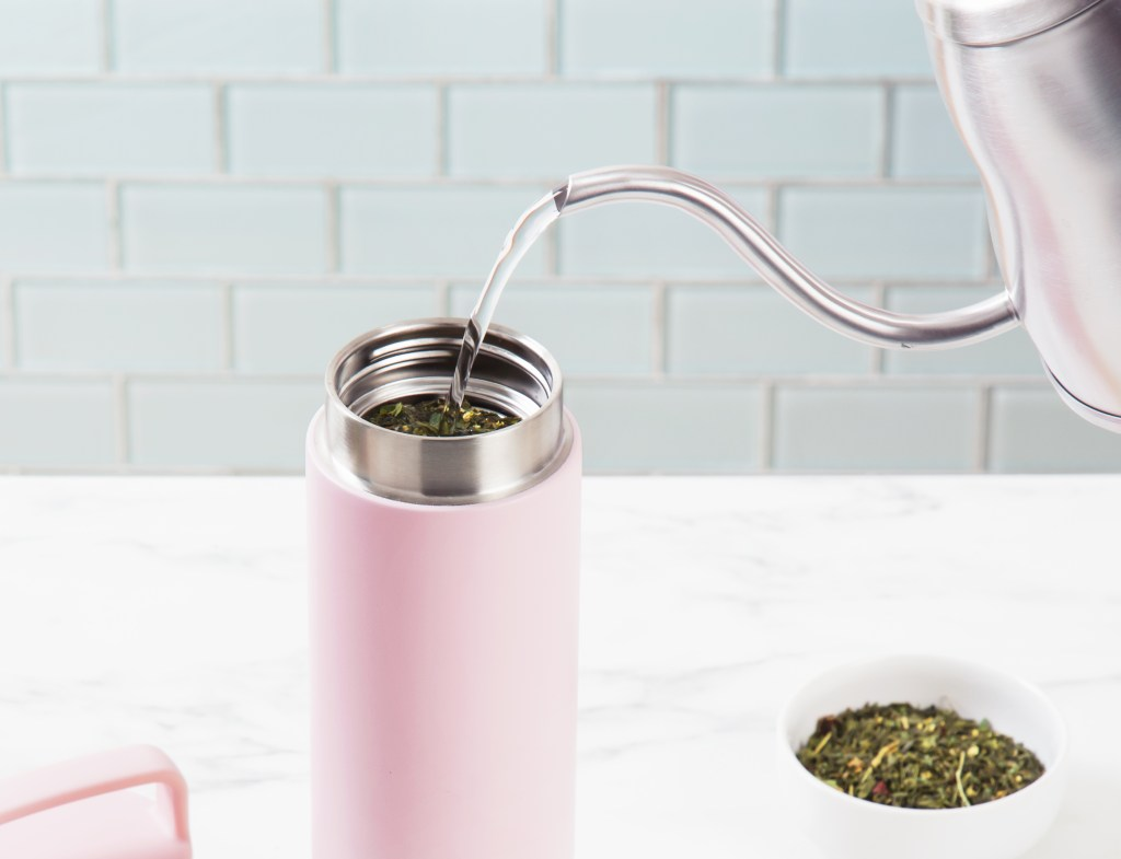 Water is seen being poured over tea leaves in a Welly Bottle tea-infusing bamboo water bottle