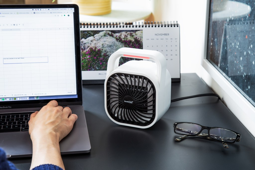 A person is seen working at their desk with a GeekHeat personal heater keeping them warm