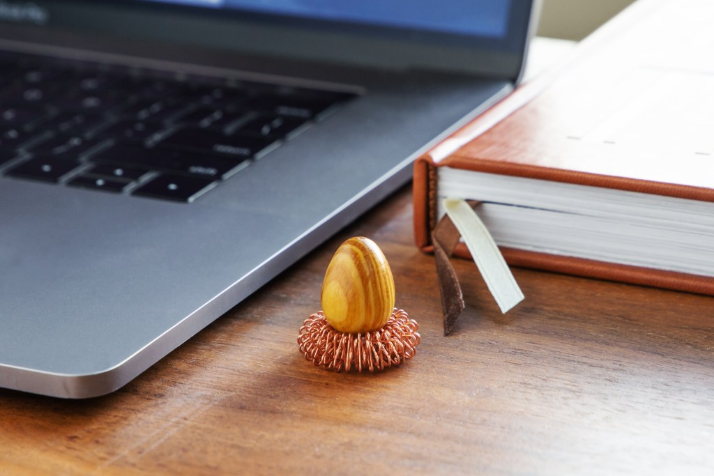 A wooden thinking egg from Orijin Design Company sits on a desk