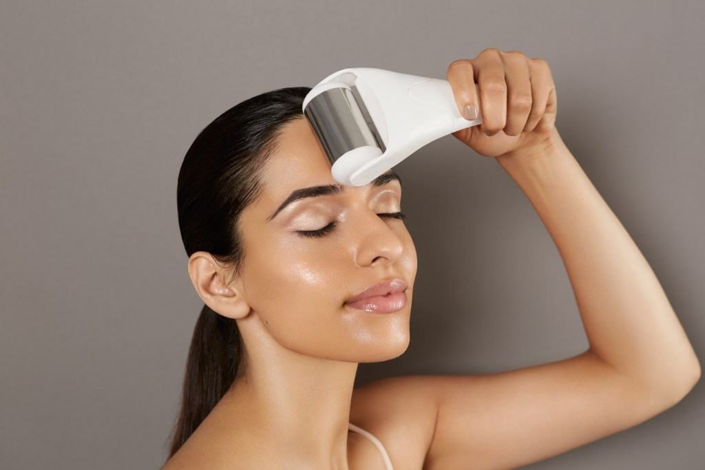 A woman is seen rolling a StackedSkincare facial ice roller over her forehead