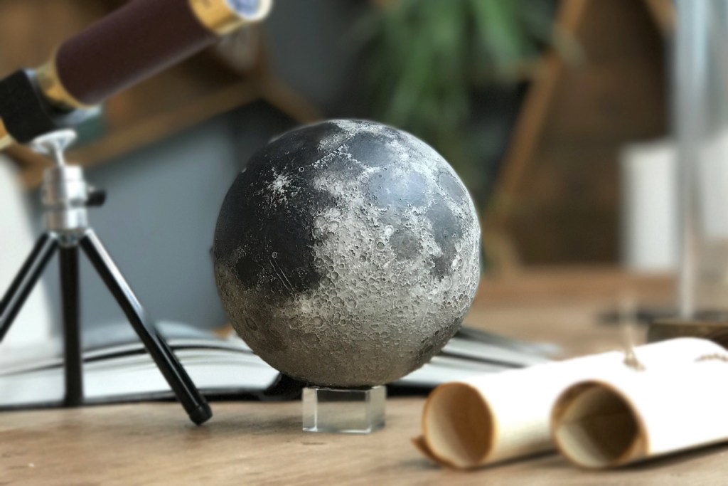 a 3D augmented reality sculpture of the moon from AstroReality is seen on a table