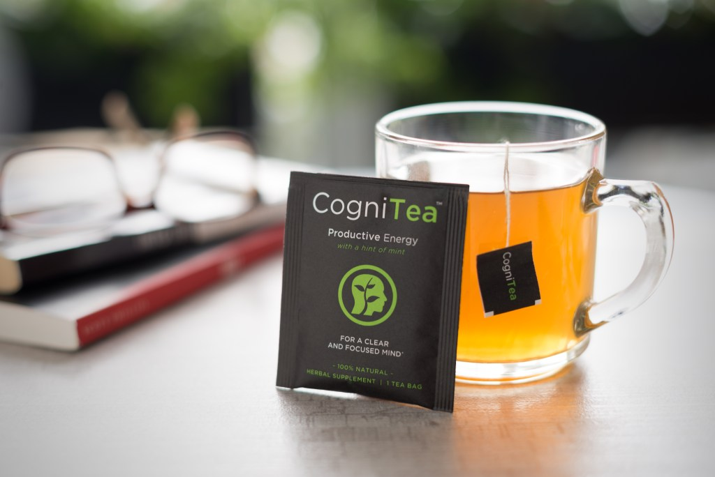 A hot cup of freshly brewed CogniTea sits on a desk