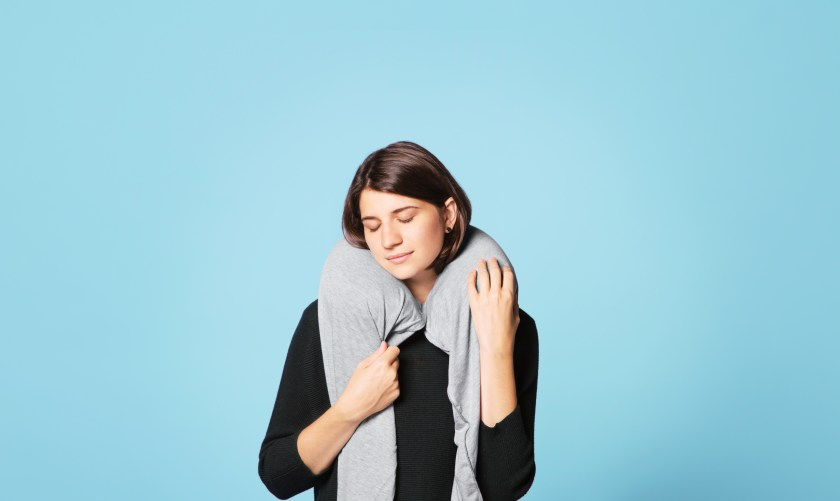 A woman is seen cozying up with her grey Sleeper Scarf with bulit-in travel pillow