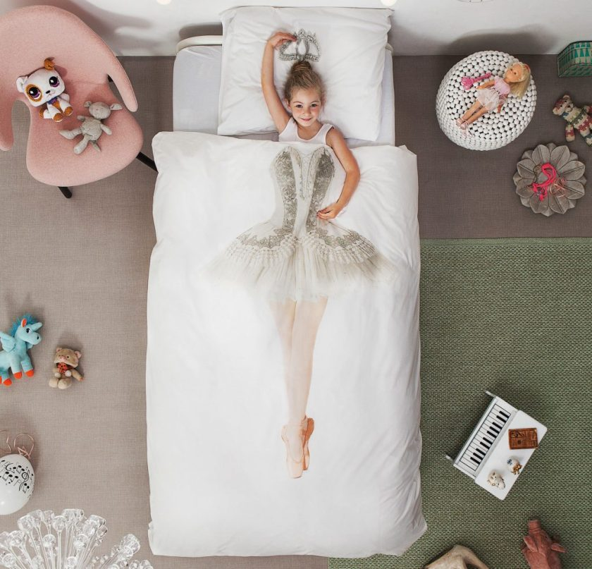 A little girl is seen laying in bed under a Ballerina duvet cover from Snurk Living