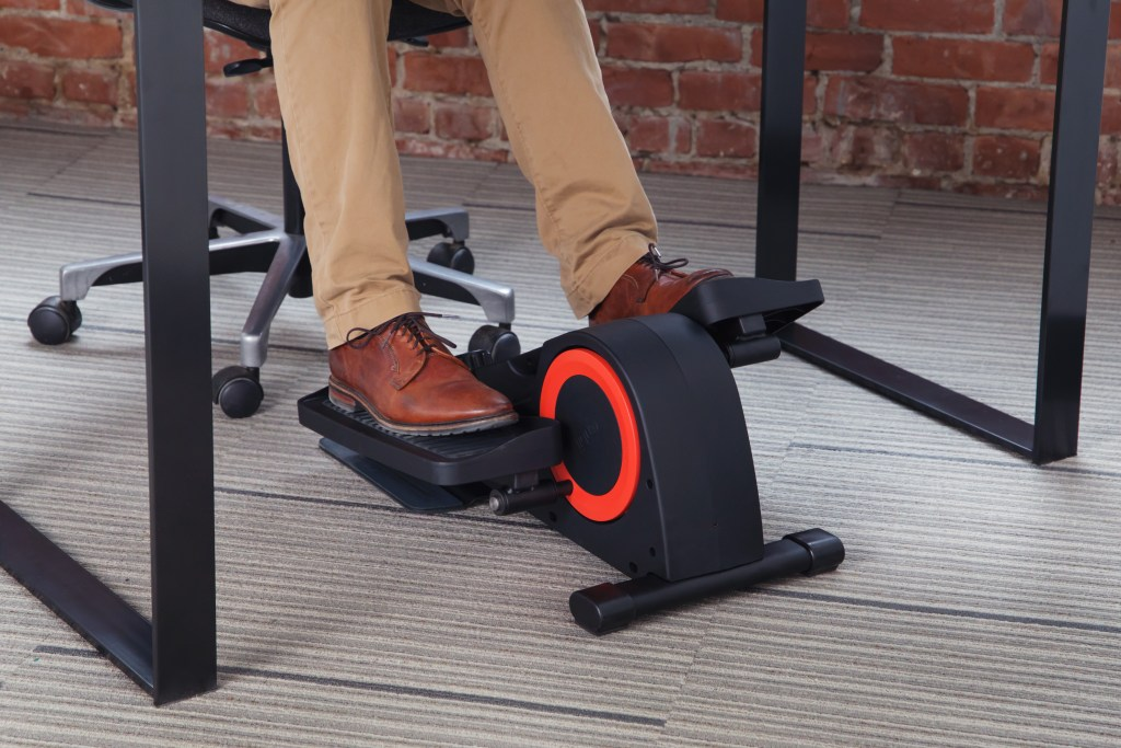 A man is seen pedaling under his desk using Cubii's under desk elliptical